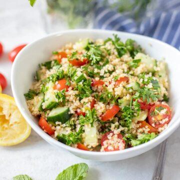 Tabouli in white bowl next to fresh herbs