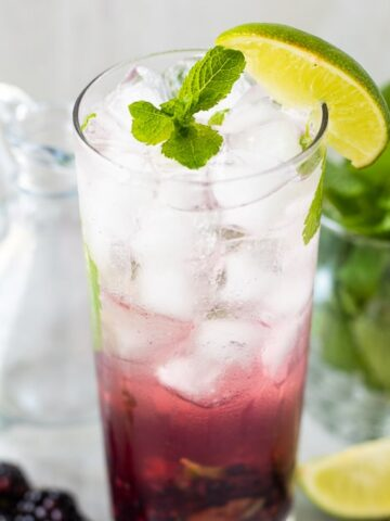 Glass of blackberry mojito garnished with mint leaves