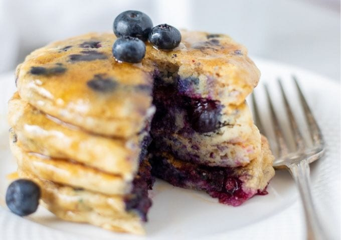 Blueberry Pancakes on white plate topped with syrup