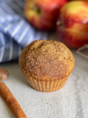 Applesauce muffin next to apples and cinnamon stick