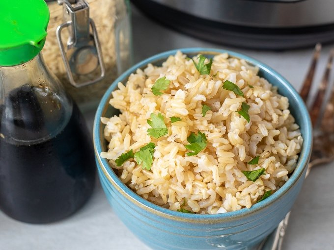 Instant Pot Brown Rice in blue bowl next to soy sauce