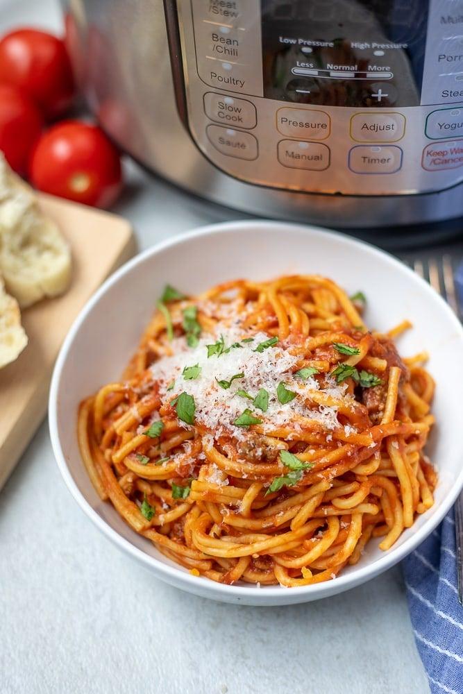 Bowl of Instant Pot Spaghetti next to Instant Pot