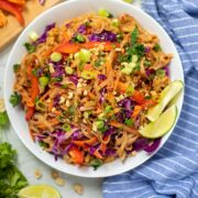 White Bowl filled with peanut noodles topped with fresh vegetables and limes on the side