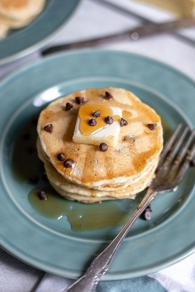 Stack of chocolate chips pancakes on blue plate with syrup