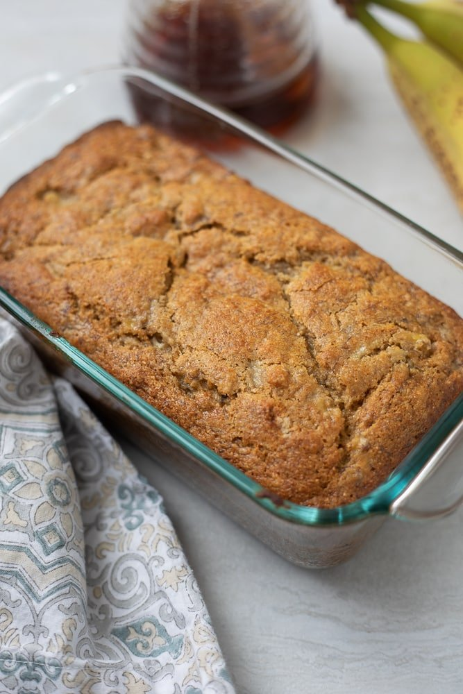 Banana Bread in glass loaf pan next to honey