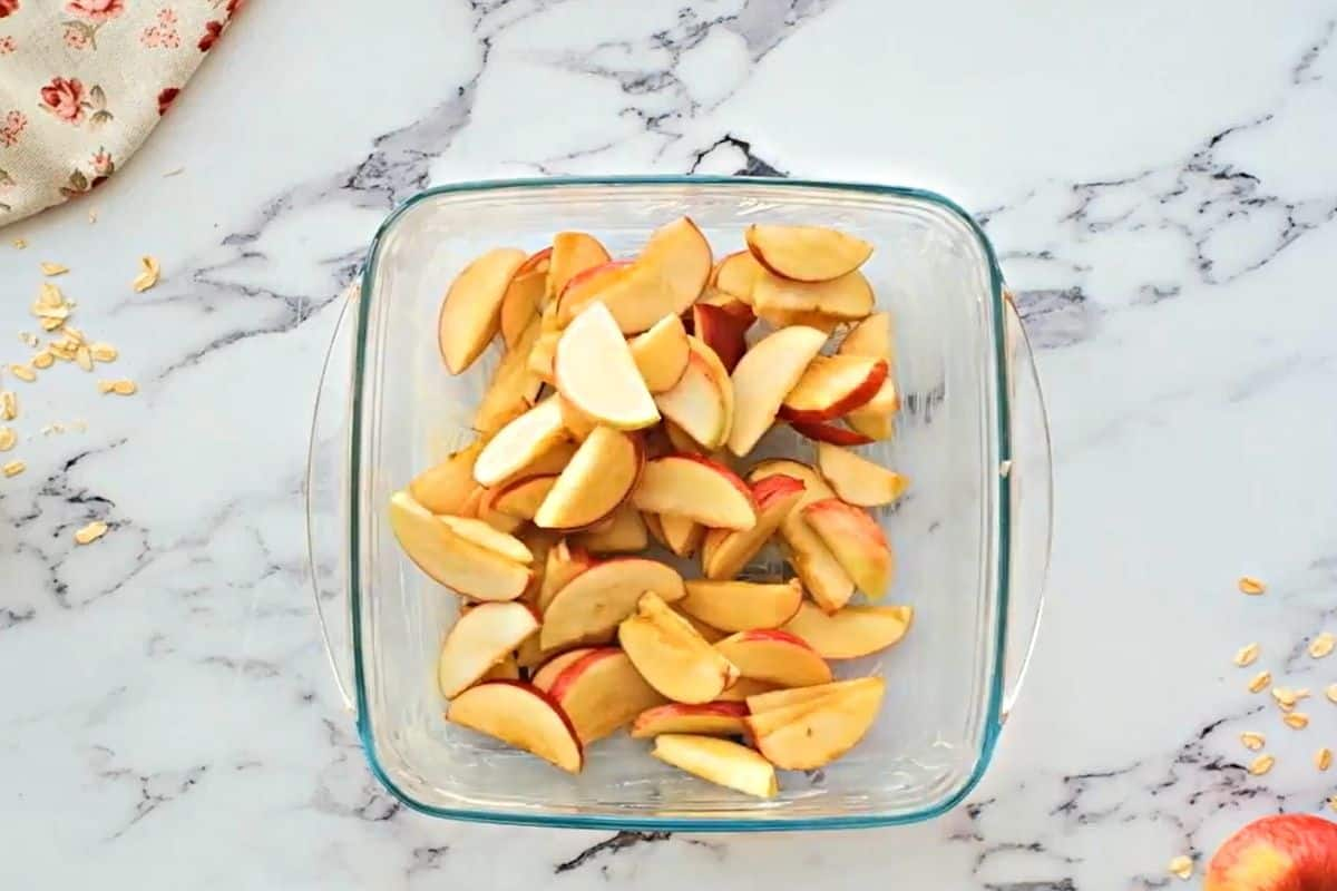 Apples in buttered baking dish.