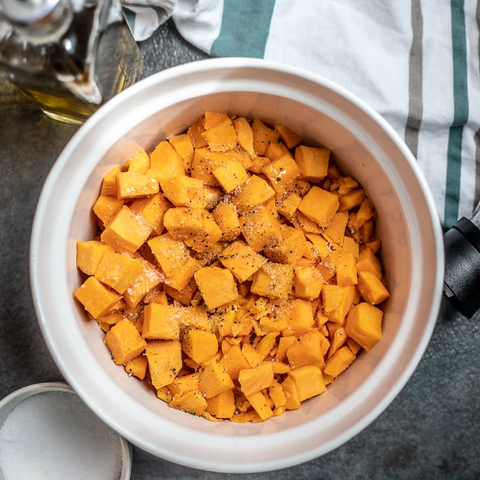 Bowl of cubed butternut squash seasoned with olive oil and salt and pepper