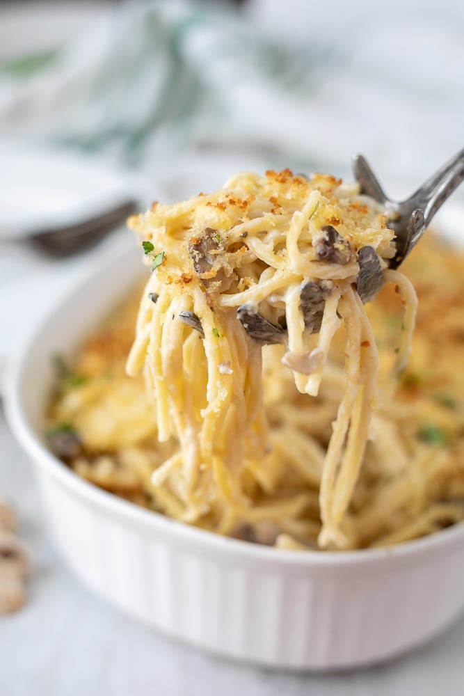 Spoonful of Turkey Tetrazzini coming from white casserole dish