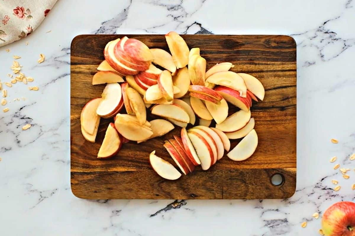 Sliced apples on a wooden cutting board.