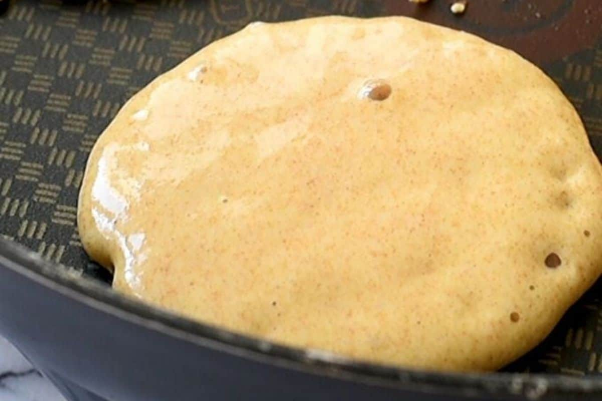 Pancake with bubbles in skillet.