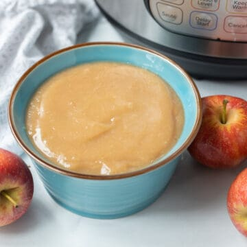 Bowl of instant pot applesauce next to instant pot.