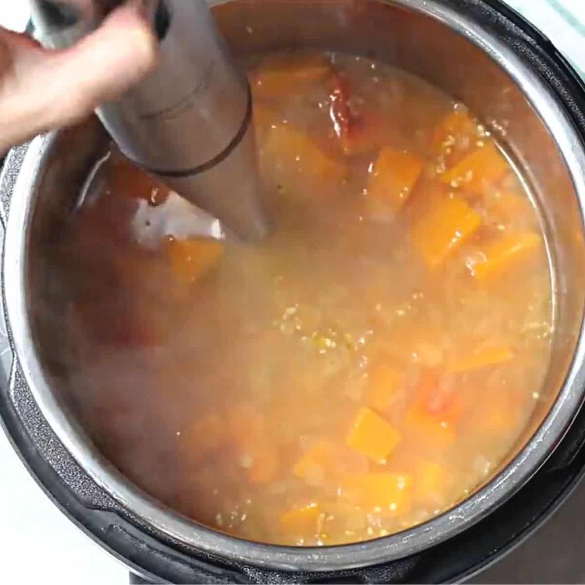 Immersion blender blending squash soup insider inner pot of instant pot.