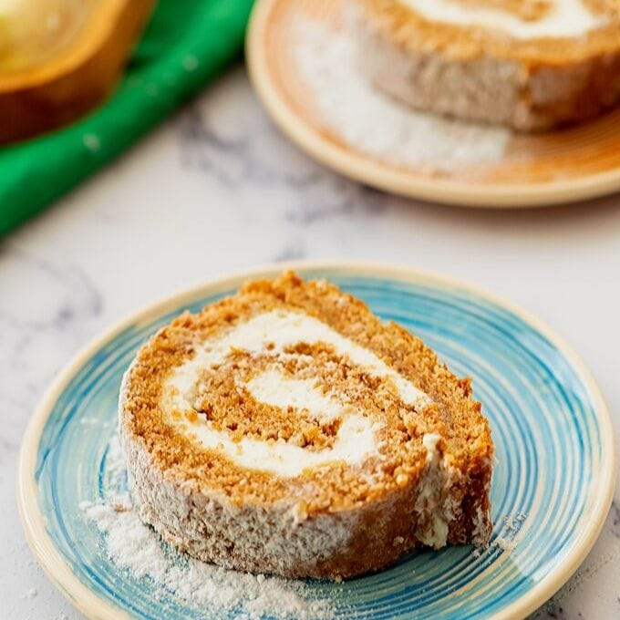 Sliced Pumpkin Roll on Blue Plate with Cream Cheese Swirl