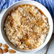 Bowl of slow cooker oatmeal topped with maple syrup and nuts