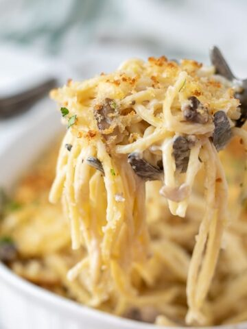 Spoonful of Turkey Tetrazzini on spoon coming out of casserole dish