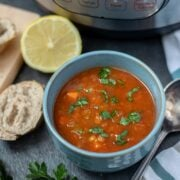 Bowl of Instant Pot Lentil Soup next to fresh lemons and Italian Bread