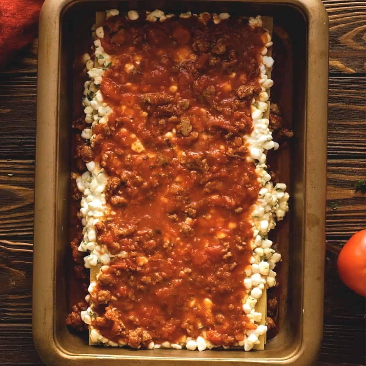 Layered lasagna in 9x18 baking pan.