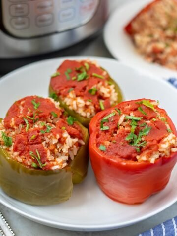 Instant Pot Stuffed peppers on white plate next to Instant Pot