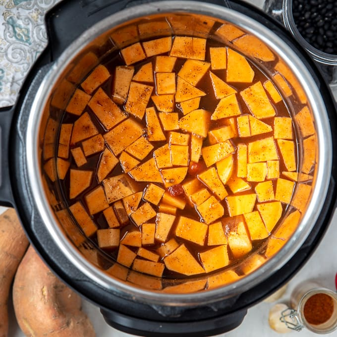 Instant Pot filled with ingredients for Sweet Potato Black Bean Chili