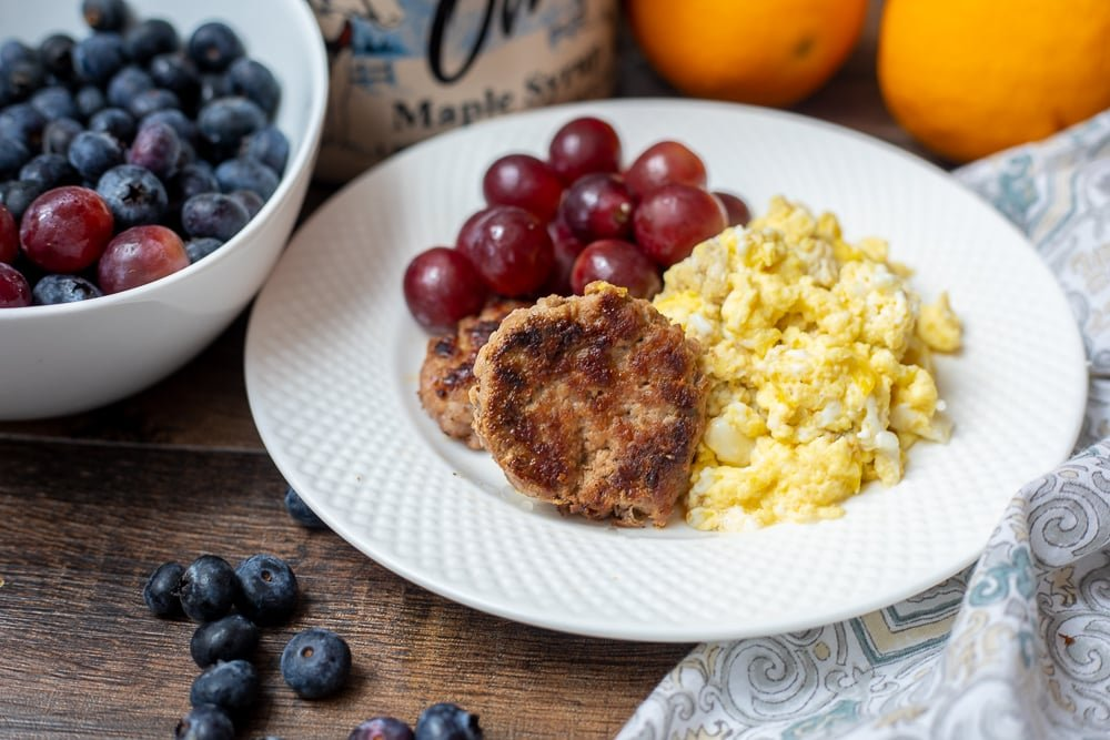 Plate of breakfast sausage and eggs with fruit.