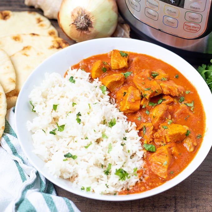 Bowl of Instant Pot Butter Chicken with rice next to Instant Pot