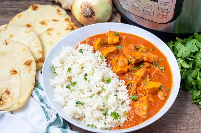 Bowl of Butter Chicken next to Naan and Instant Pot