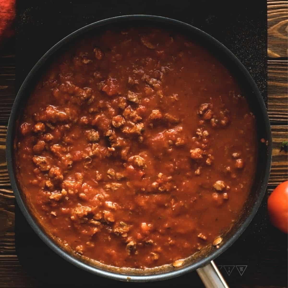 Ground beef mixed with tomato sauce and water in skillet.