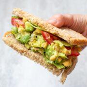 Cut open chickpea sandwich being held