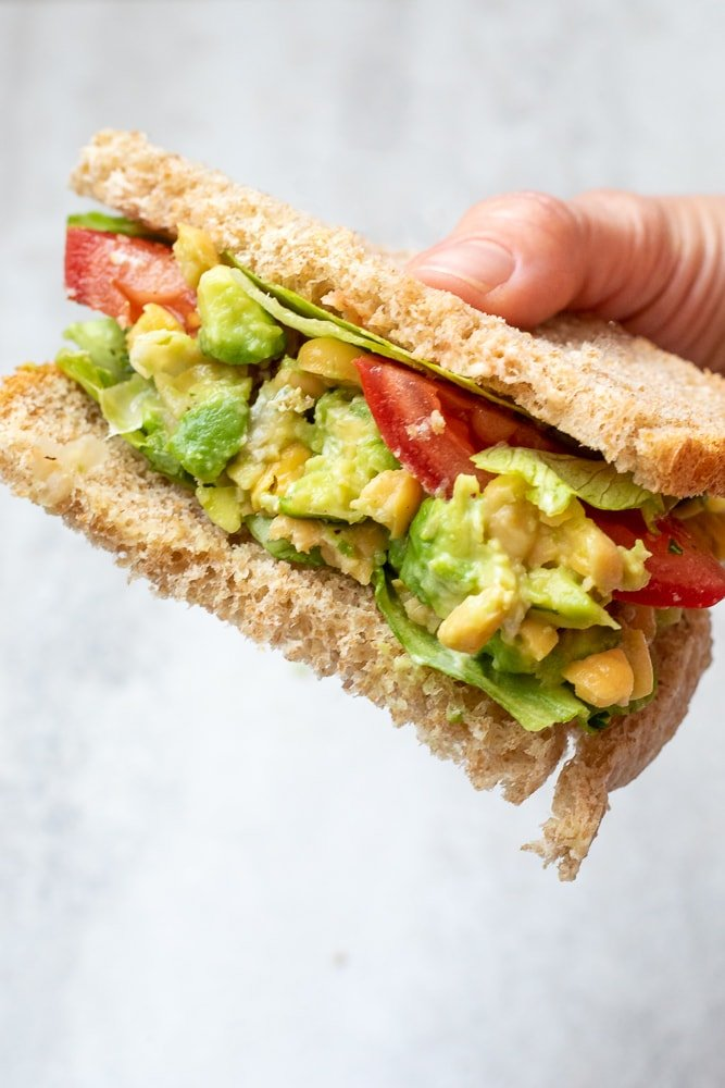 Chickpea Salad Sandwich cut open to show mashed chickpeas with avocado