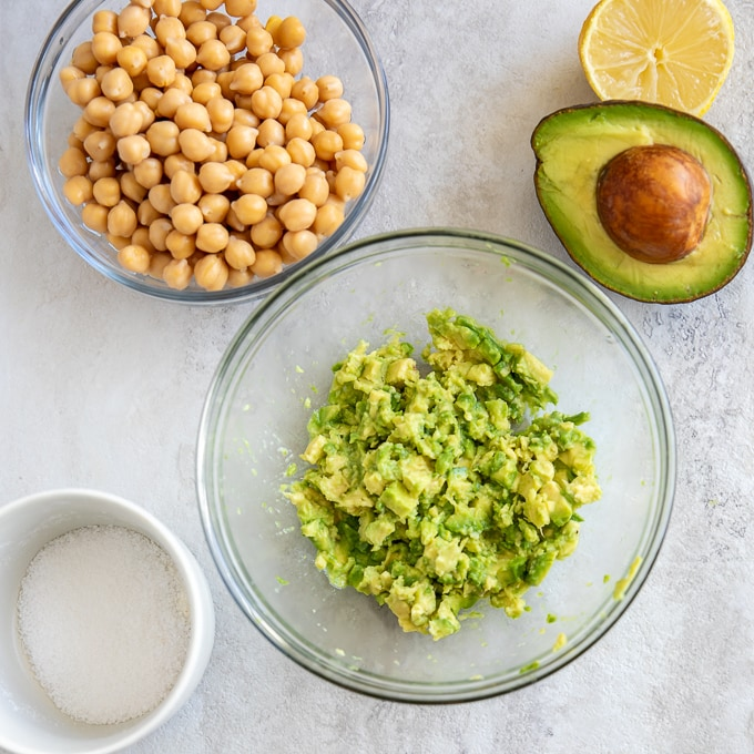 Mashed Avocado in glass bowl with chickpeas next to the bowl
