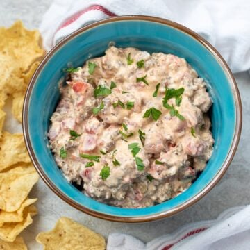 Cream Cheese Sausage Dip in bright blue with chips next to bowl