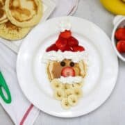 Pancake decorated with strawberries and whipped cream to look like santa.