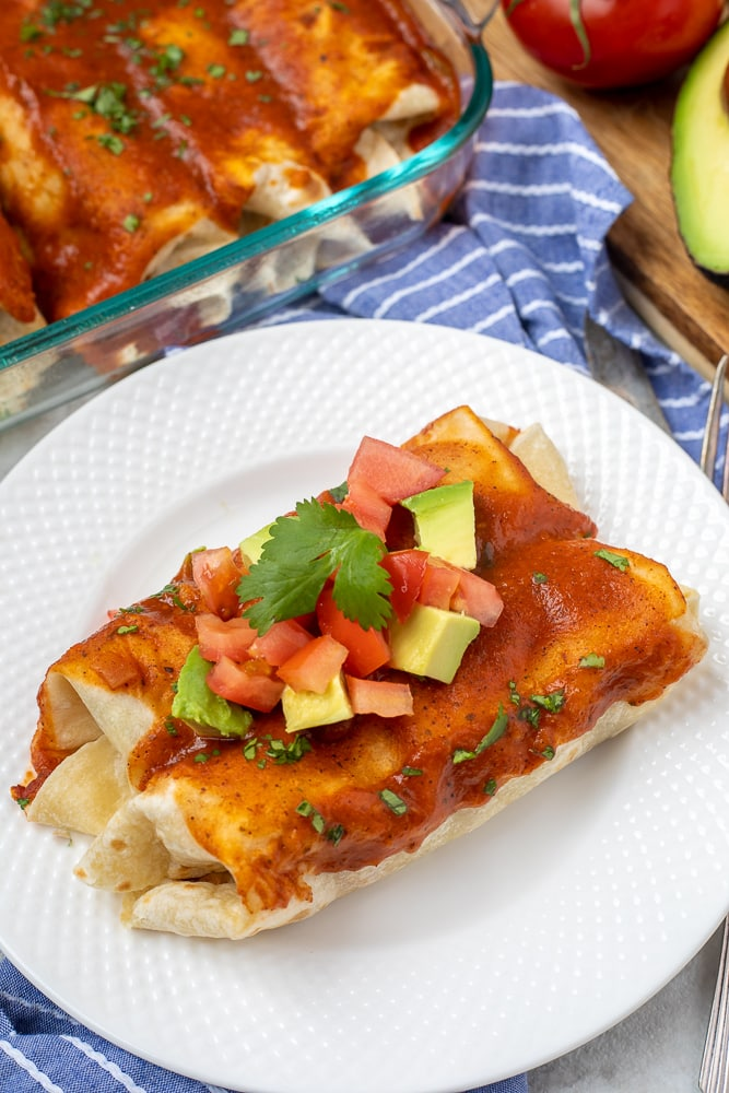 2 vegetable enchiladas on white plate topped with avocado