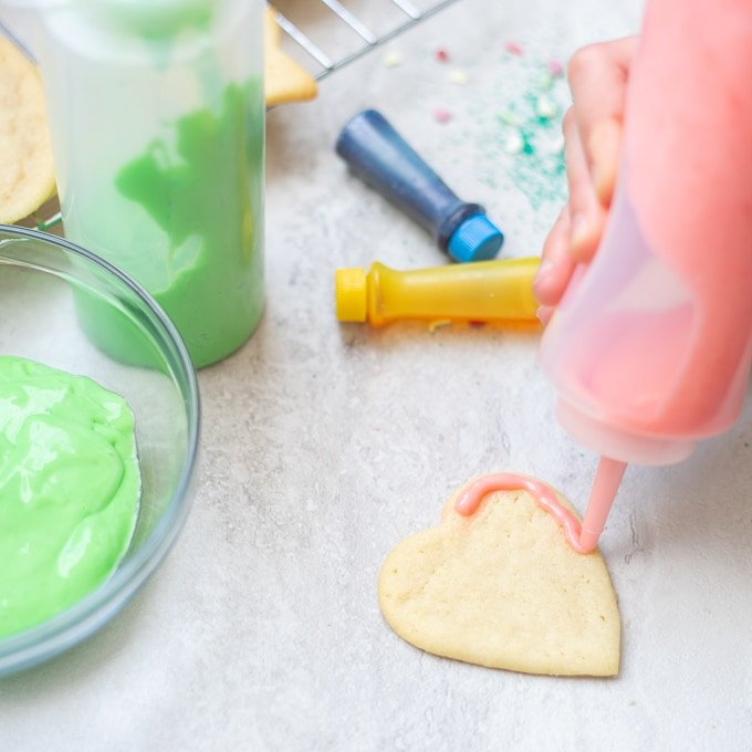 Condiment bottle piping frosting onto heart sugar cookie