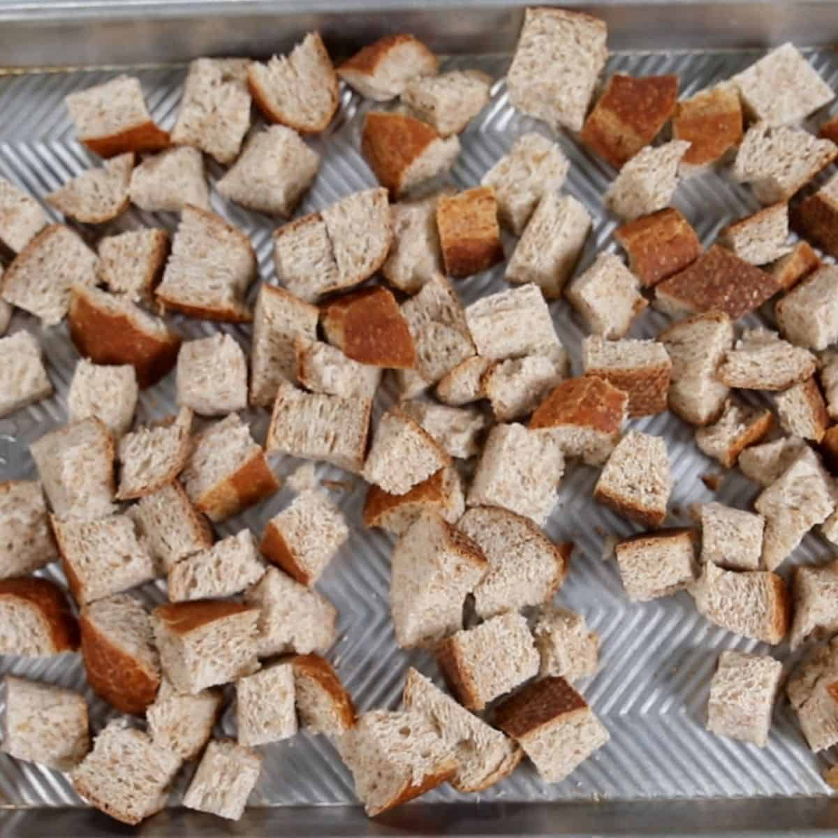 Cubed wheat bread on sheet pan.