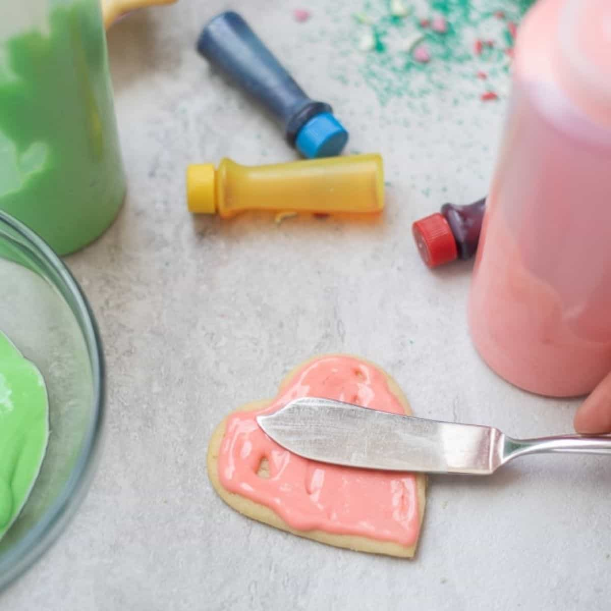 Spreading icing on sugar cookie with small spatula