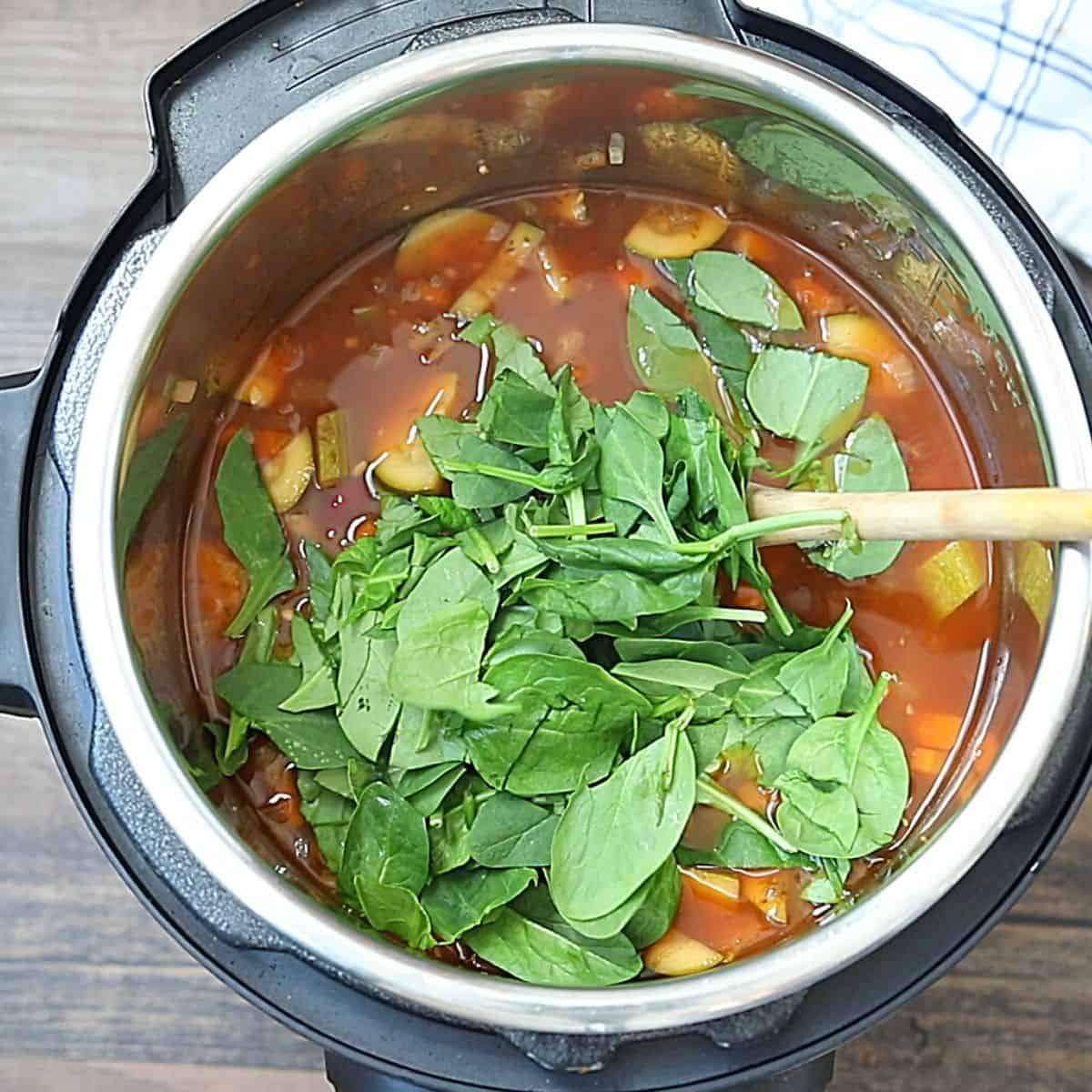 Spinach on top of cooked minestrone in instant pot.