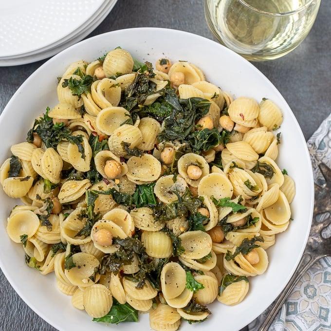 Orecchiette pasta with chickpeas and kale in white dish