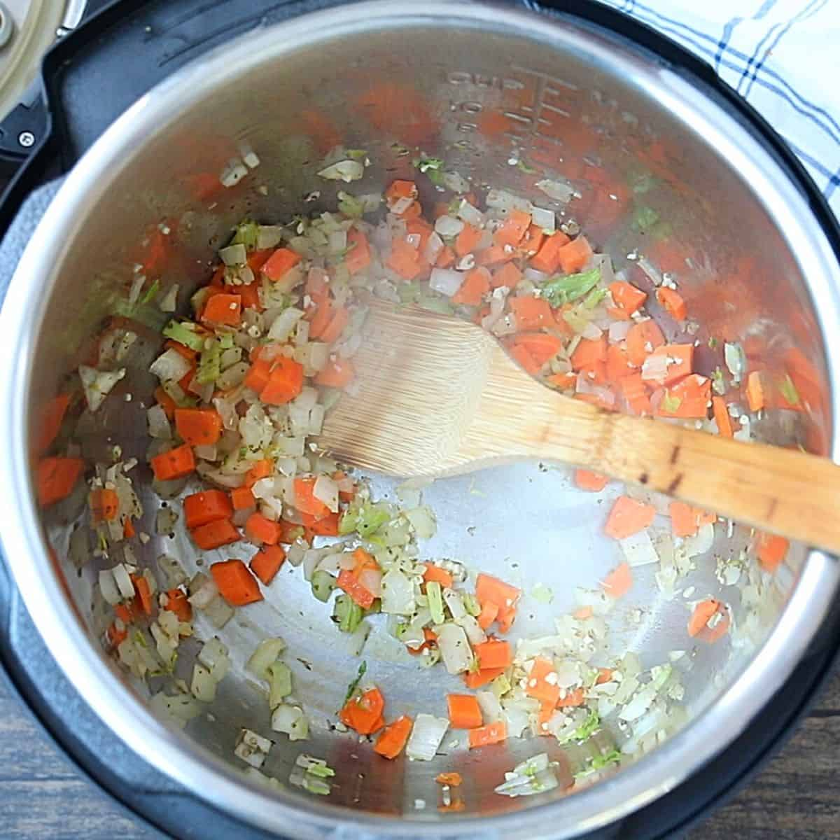 Onions, celery, and carrots sauteed in inner pot of instant pot.