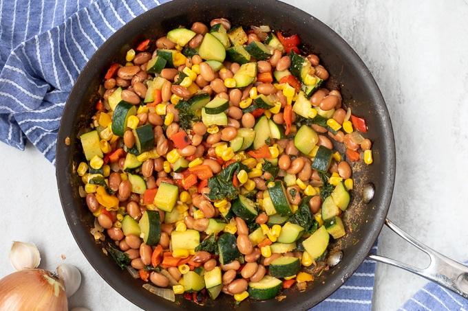 Skillet with vegetable mixture for vegan enchiladas