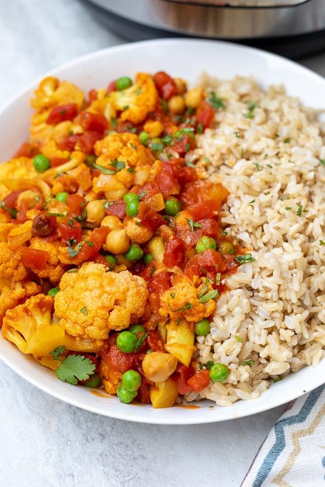 Cauliflower Tikka Masala in white dish with brown rice