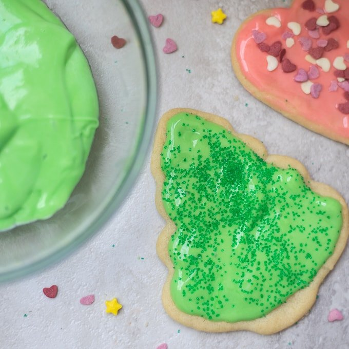 Frosted Christmas Tree next to frosted heart sugar cookie