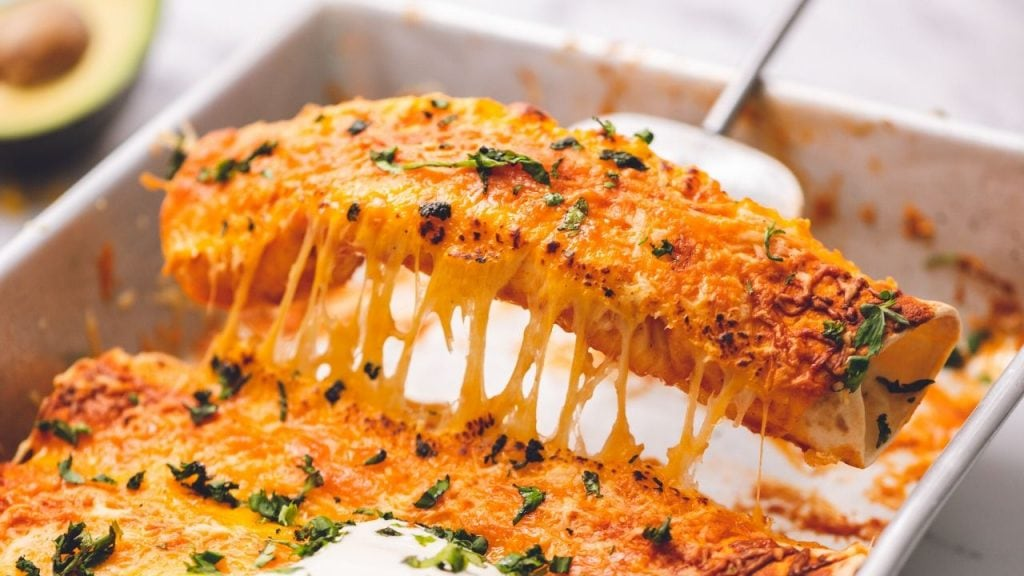 Chicken Enchilada Being pulled out of baking dish