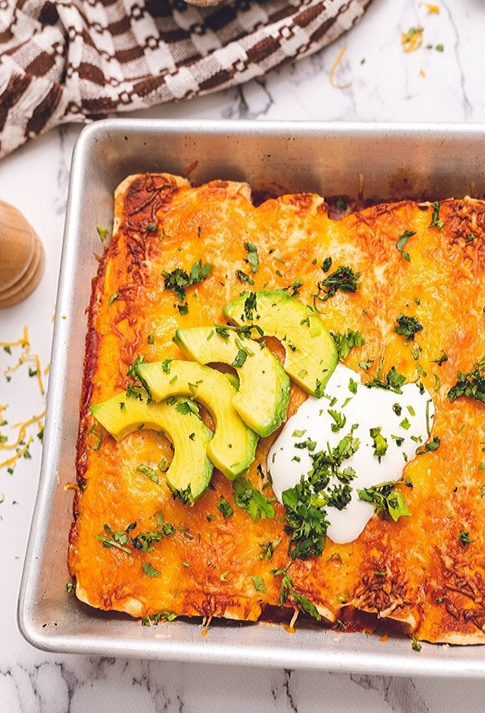 Baked Chicken Enchiladas topped with avocado and sour cream