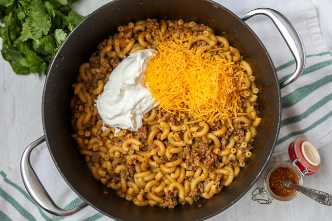Taco Pasta in skillet with shredded cheese and sour cream