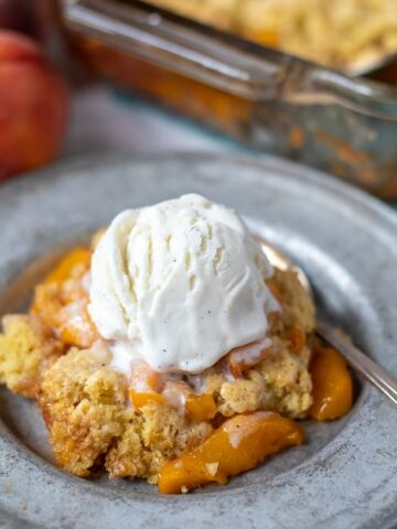 Peach Cobbler topped with vanilla ice cream on silver plate