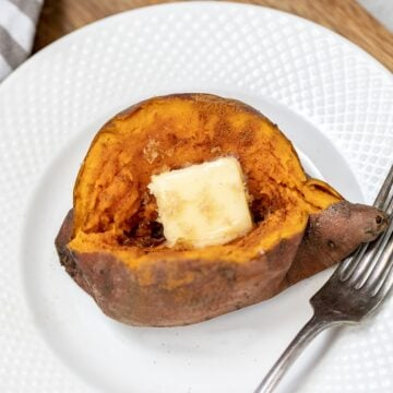 Instant Pot Sweet Potato on white plate topped with butter and cinnamon sugar