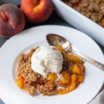 Peach Crisp dished out in white bowl with vanilla ice cream