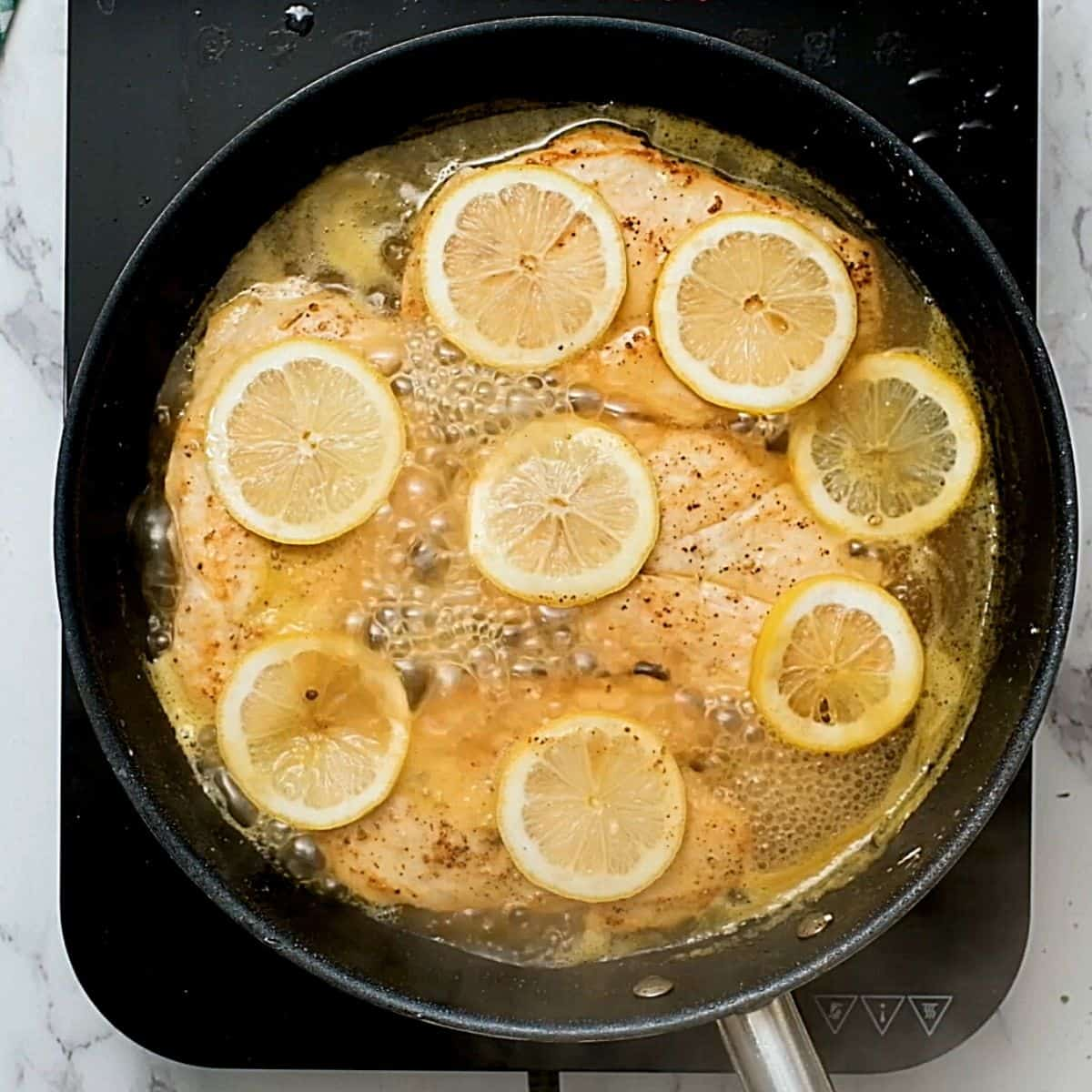Chicken cutlets in a skillet topped with lemon slices.