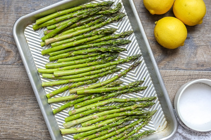 Raw Asparagus on baking sheet next to salt and lemons